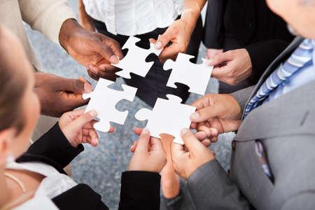 piezas de puzzle: Close-up Foto De Empresarios Holding Jigsaw Puzzle