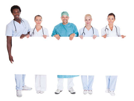 medical clinic: Group Of Multiracial Doctors Holding Placard Over White Background
