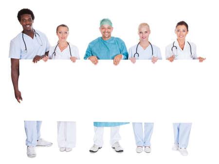 držení: Skupina mnohonárodnostní Lékaři drží transparent Na Bílém Pozadí
