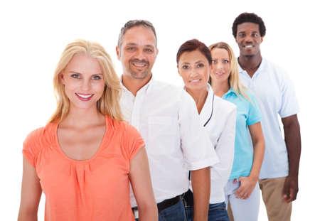 Grupo de personas multirraciales pie en una fila en el fondo blanco Foto de archivo