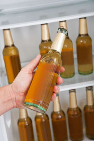 Man choosing bottle of beer from a refrigerator photo