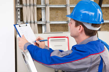 cable tv: Portrait of young construction worker writing on clipboard