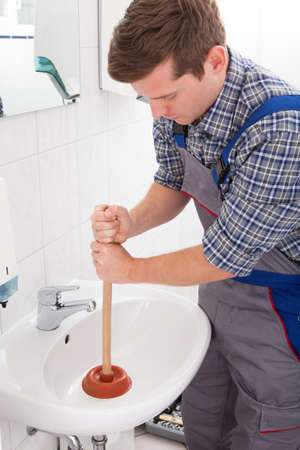 stoppage: Portrait of male plumber pressing plunger in sink