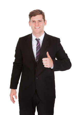 Portrait of businessman showing thumb up sign isolated on white background photo