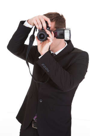 Portrait of paparazzi capturing photograph on white background photo