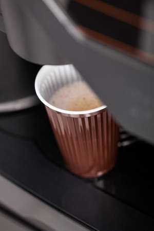 with coffee maker: Coffee maker pouring hot espresso coffee in a glass