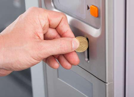 Primer plano de la mano del hombre que inserta la moneda en la máquina expendedora