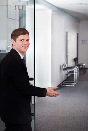 Portrait of young businessman welcoming at door photo