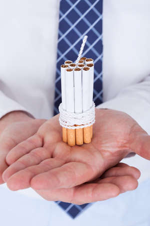 Close-up Of Businessman Holding Cigarettes Tied With Rope And Wick Stock Photo - 21328472