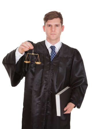 Male Lawyer Holding Weight Scale And Book Over White Background photo