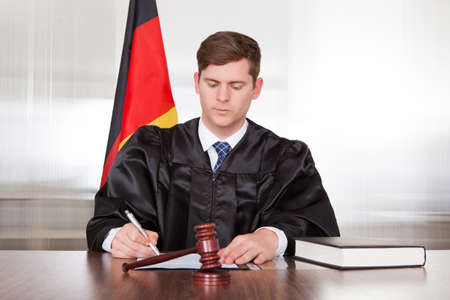 Male Judge With The Gavel And Book In Courtroom photo