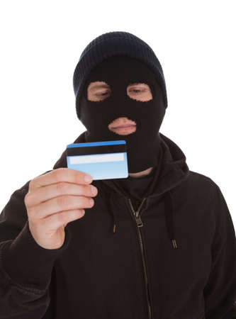 Burglar Wearing Mask Holding Credit Card Over White Background photo