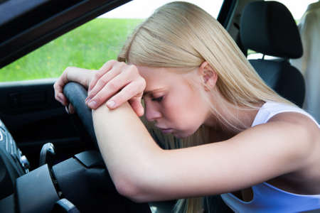 trouble: Exhausted Woman Leaning Head On Steering Wheel Stock Photo