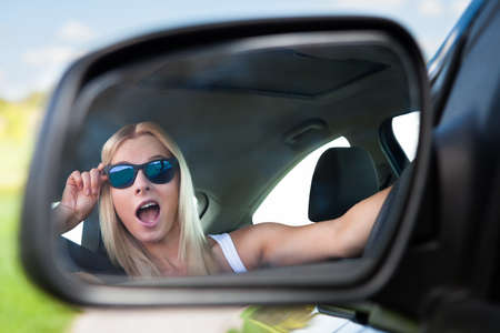 Young Blonde Woman Wearing Sunglasses Driving Car photo