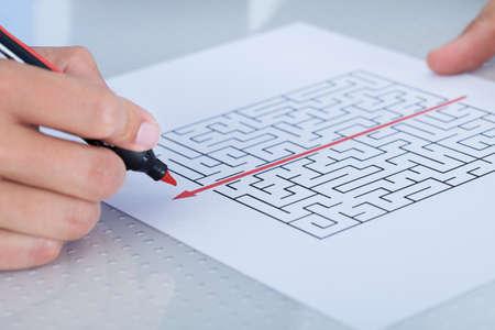 shortcut: Businessman Solving Maze Puzzle With Red Pen Stock Photo