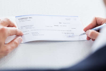 canadian cash: A Male Hand Filling Out The Amount On A Cheque