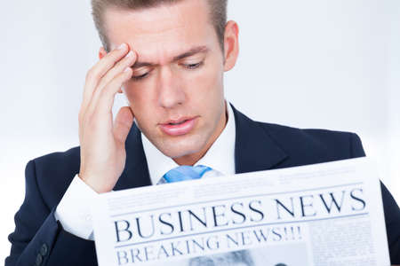 breaking news: Young Businessman Reading Breaking News On Newspaper Stock Photo