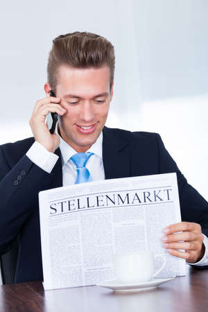 Businessman Reading Newspaper With The Headline Stellenmarkt photo