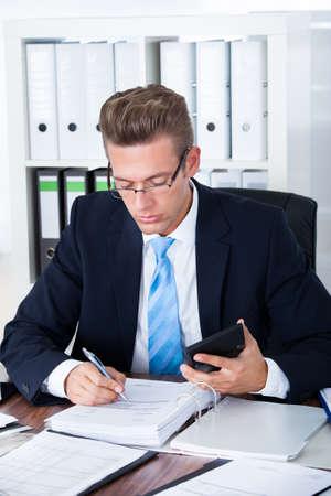 Portret Van Jonge Zakenman Met Calculator In Office Stockfoto