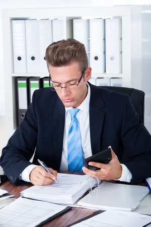auditor�a: Retrato del hombre de negocios joven que usa la calculadora en oficina Foto de archivo