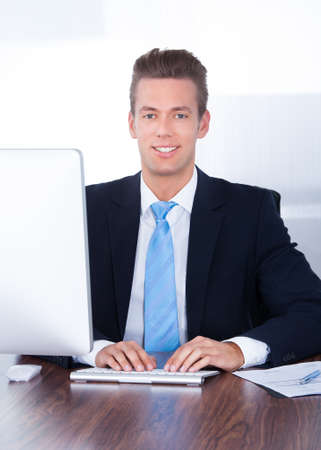 Portrait Of Happy Young Businessman Using Computer In Office Stock Photo - 21328536