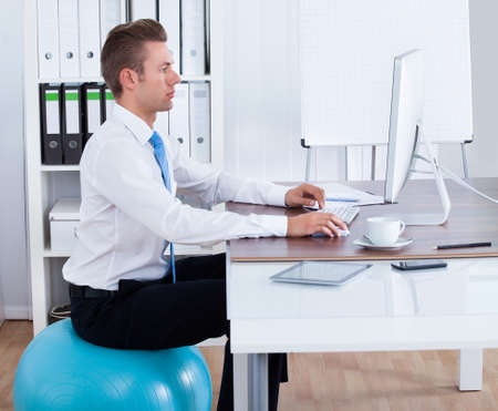workplace wellness: Businessman Sitting Comfortably On Pilates Ball And Using Computer In Office