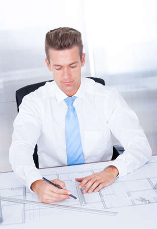 Portrait Of Young Male Architect Working With Blueprint At Desk Stock Photo - 21328539