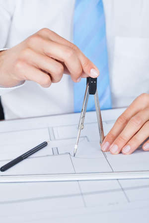 Close-up Of Male Architect Working On Blueprint At Desk Stock Photo - 21328541