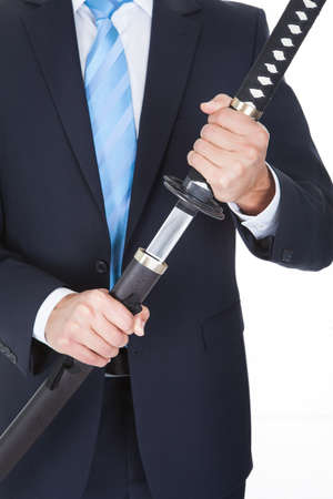 anger management: Close-up Of Businessman Removing Sword Over White Background Stock Photo