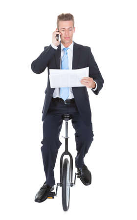 Businessman Sitting On Unicycle Talking On Cellphone Over White Background photo