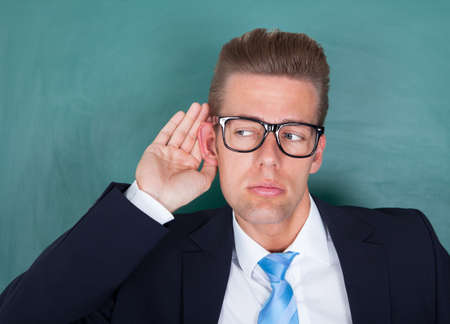 listen ear: Male Lecturer Standing In Front Of Chalkboard And Trying To Listen