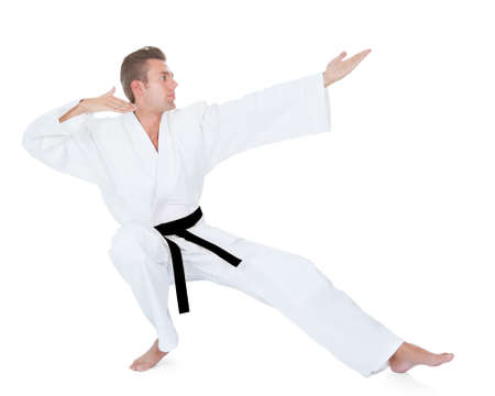 stance: Young Man In Kimono Practicing Karate Over White Background Stock Photo