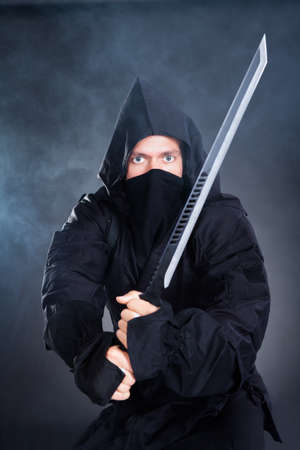 Portrait Of Male Ninja In Black Costume Holding Sword photo