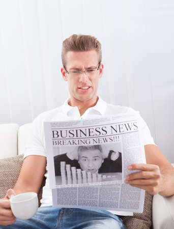 Man Reading Newspaper With The Headline Breaking News photo