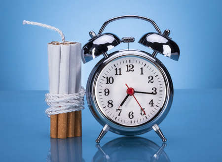 Cigarettes Tied With Rope And Alarm Clock Over Blue Background Stock Photo - 21328844