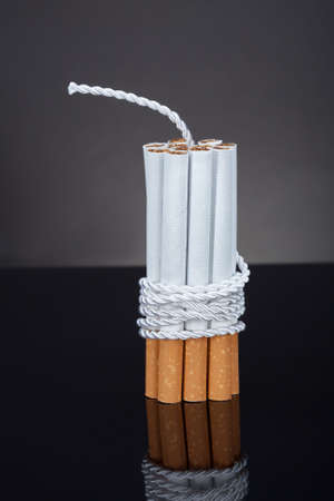 Cigarettes Tied With Rope And Wick Over Blue Background photo