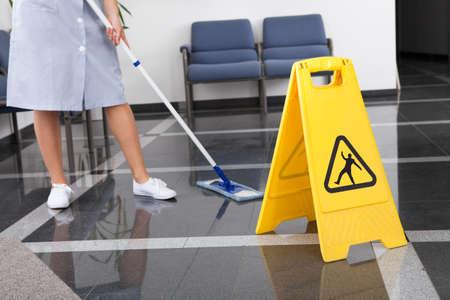 Cameriera pulizia del pavimento con la scopa in ufficio Archivio Fotografico - 21328893