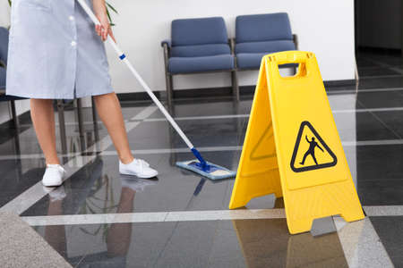 mops: Maid Cleaning The Floor With Mop In Office