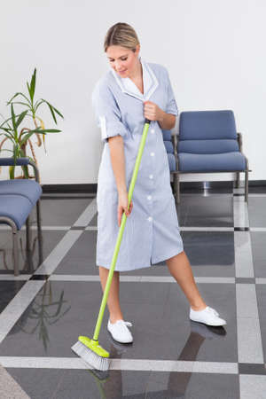 housekeeping: Limpieza que limpia el suelo con la fregona en oficina