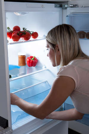 Young Woman Looking For Something In Refrigerator photo