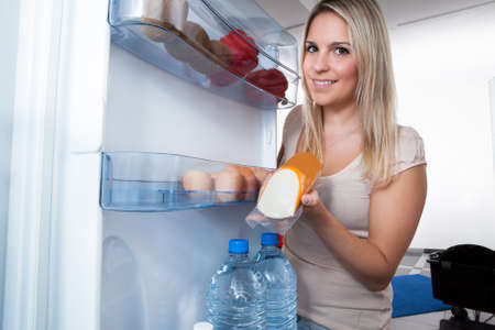 cold storage: Young Blonde Woman Taking Sausage From Refrigerator At Home