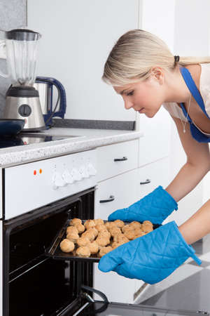 home baked: Young Woman Placing Tray Full Of Cookies In Oven Stock Photo