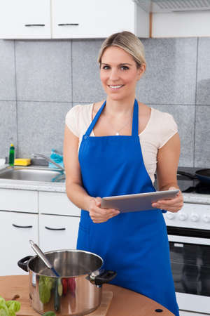 Woman Using Digital Tablet In Kitchen For Recipe photo