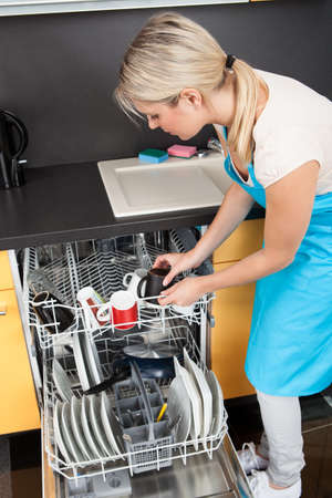 lavar platos: Mujer feliz que pone Utensilios Lavaplatos para la limpieza