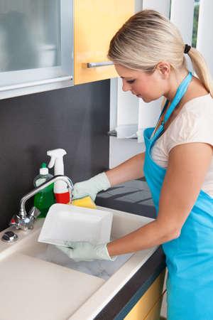 lavar platos: Mujer joven que lava la placa en la cocina