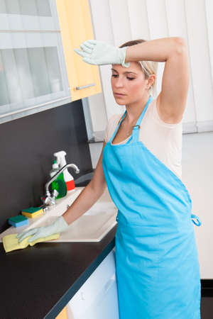 Woman Tired Cleaning Kitchen Worktop At Home Stock Photo - 21329089