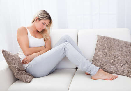 menstrual: Portrait of woman with stomach ache sitting sofa Stock Photo
