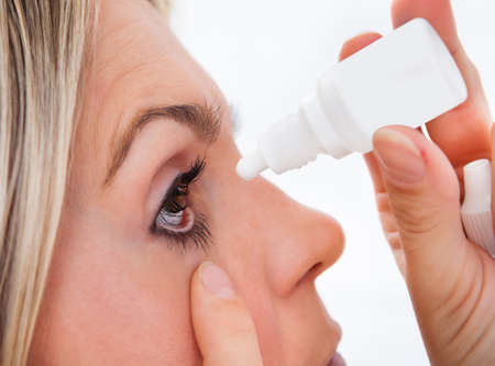 cataracts: Close up young woman pouring drops in her eyes on white background Stock Photo