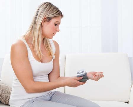 Retrato de una mujer joven que mide su presión arterial Foto de archivo
