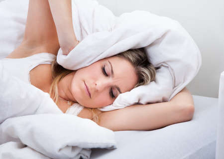 annoyed girl: Portrait of a young woman not being able to sleep Stock Photo